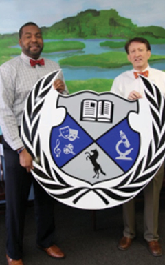 (L-R) Kevin Smith, principal at C.E. Williams Middle School for Creative and Scientific Arts, and Philip Fairchild, director of provider network operations at Select Health display the school's crest, which Smith designed.