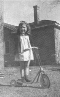 """Look Mom – No Hands!"" Nancy Campbell smiles while balancing on a scooter in her yard in Windermere.  Nancy grew up in Windermere. She has supplied many pieces of the puzzle to create the story of St. Andrew's Parish in the 1950s. (Photograph courtesy of Nancy Campbell Vick)"