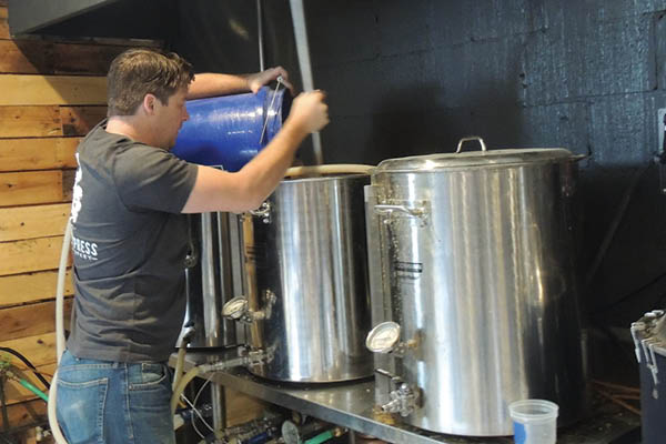 Head brewer Hunter Eisele adds grains to the brew.