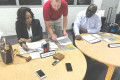 Cynthia Anderson, David Childress, and Chairman Rodney Louis huddle around phones trying to do the district and constituent board's work.