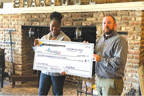 Director of the Charles Webb Center Darneyelle Washington  accepts a donation from WAJIBA president Bradley Adams